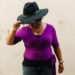 african american women in a black fedora and purple wrap top looking toward the ground