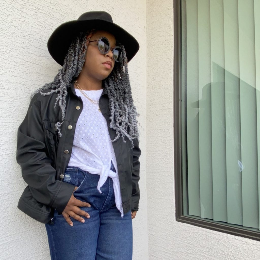 black woman with grey passion twist in a wide brim hat with leather jacket, tie front top and wide leg jeans